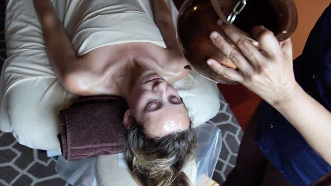 Shirodhara treatment at panchakarma wellness retreat.