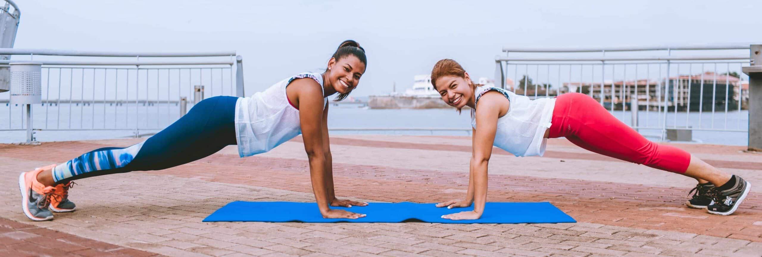 two smiling women exercising
