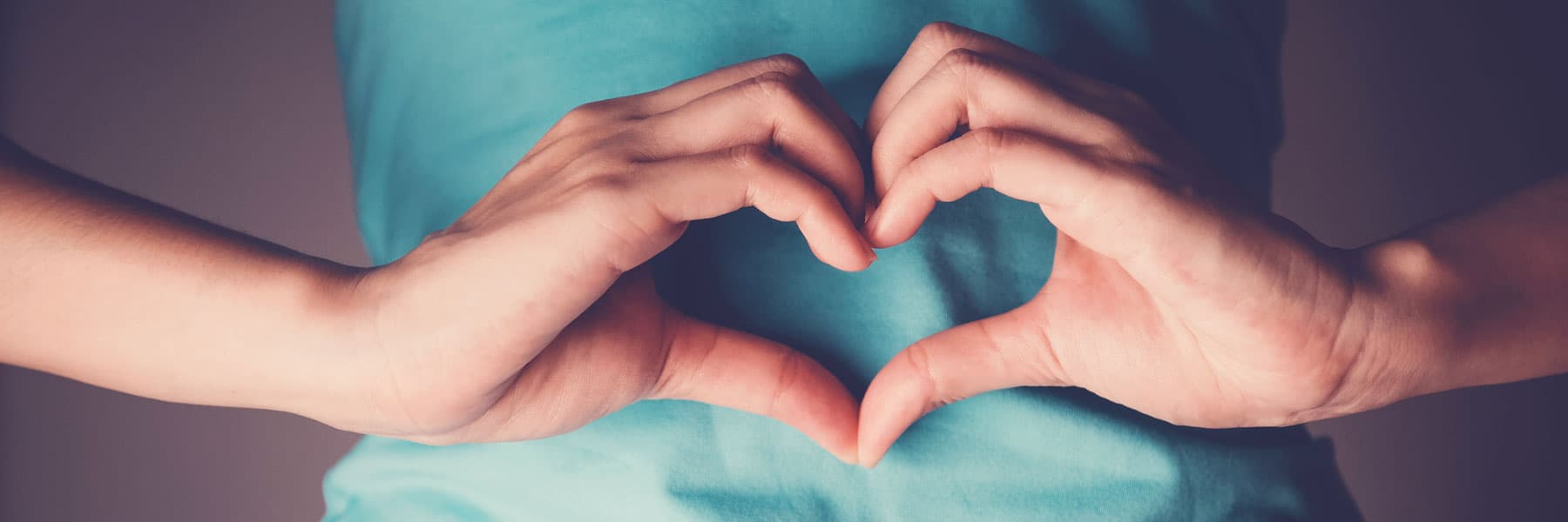 woman making heart with hands over stomach