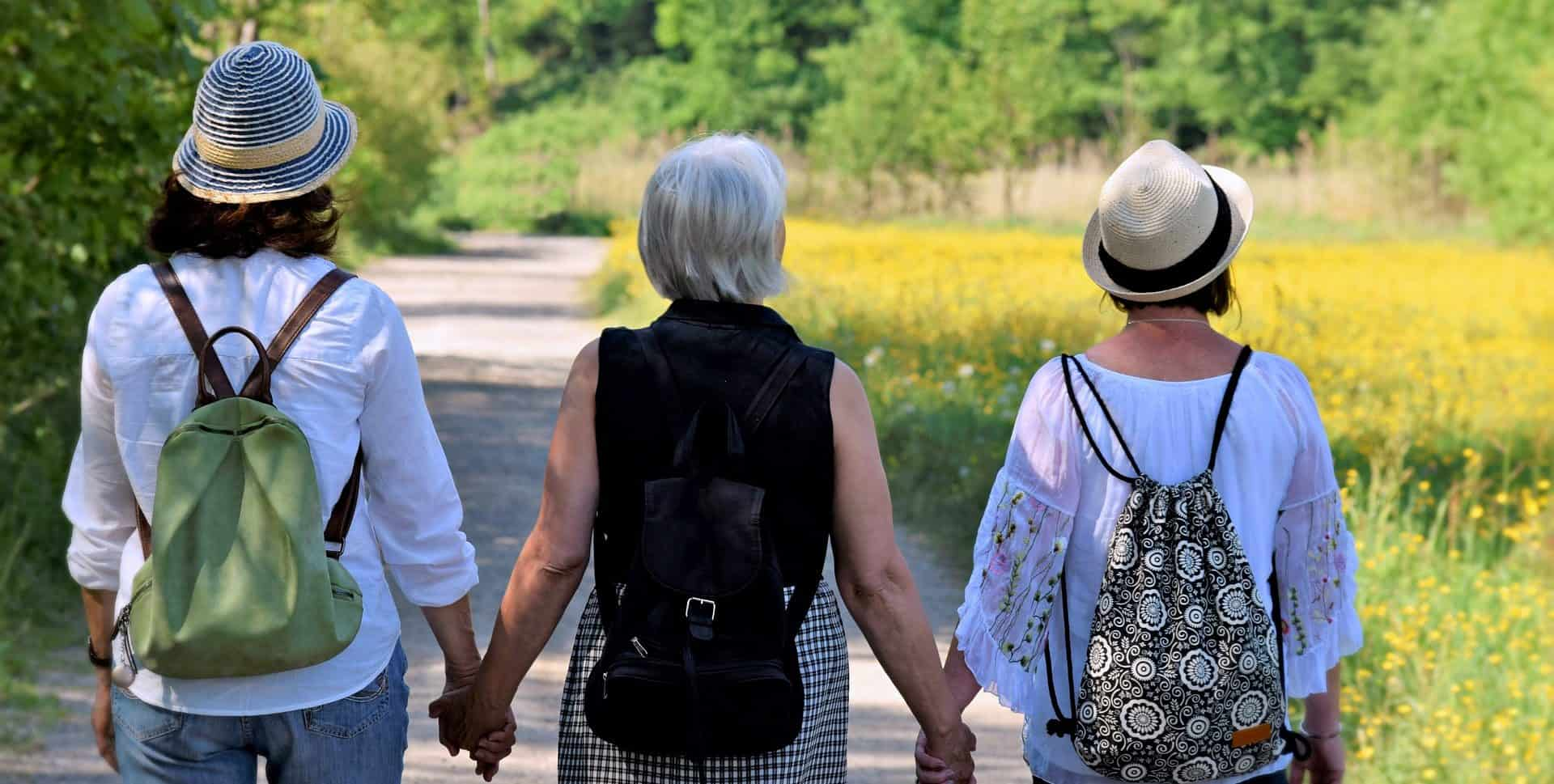 three women friends walking hand in hand down road