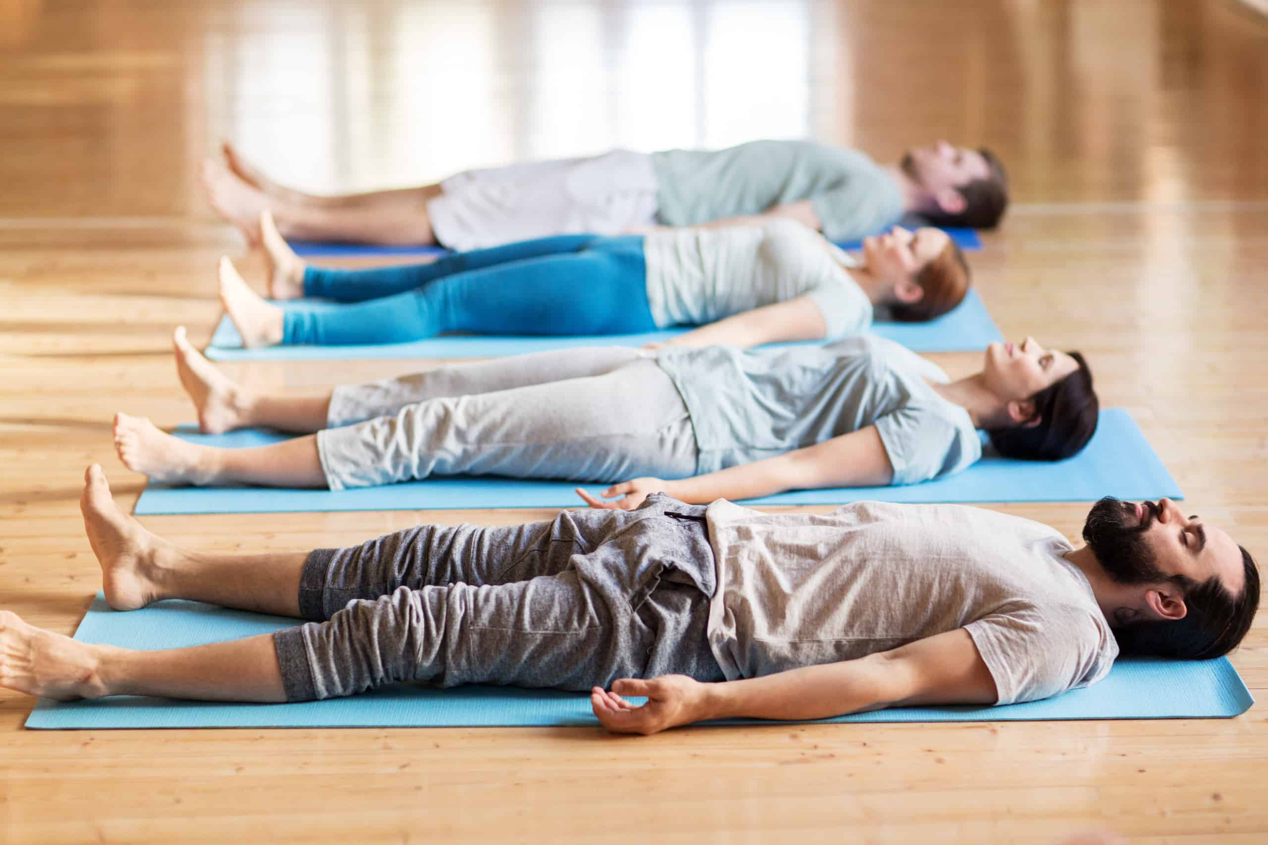yoga group in corpse pose