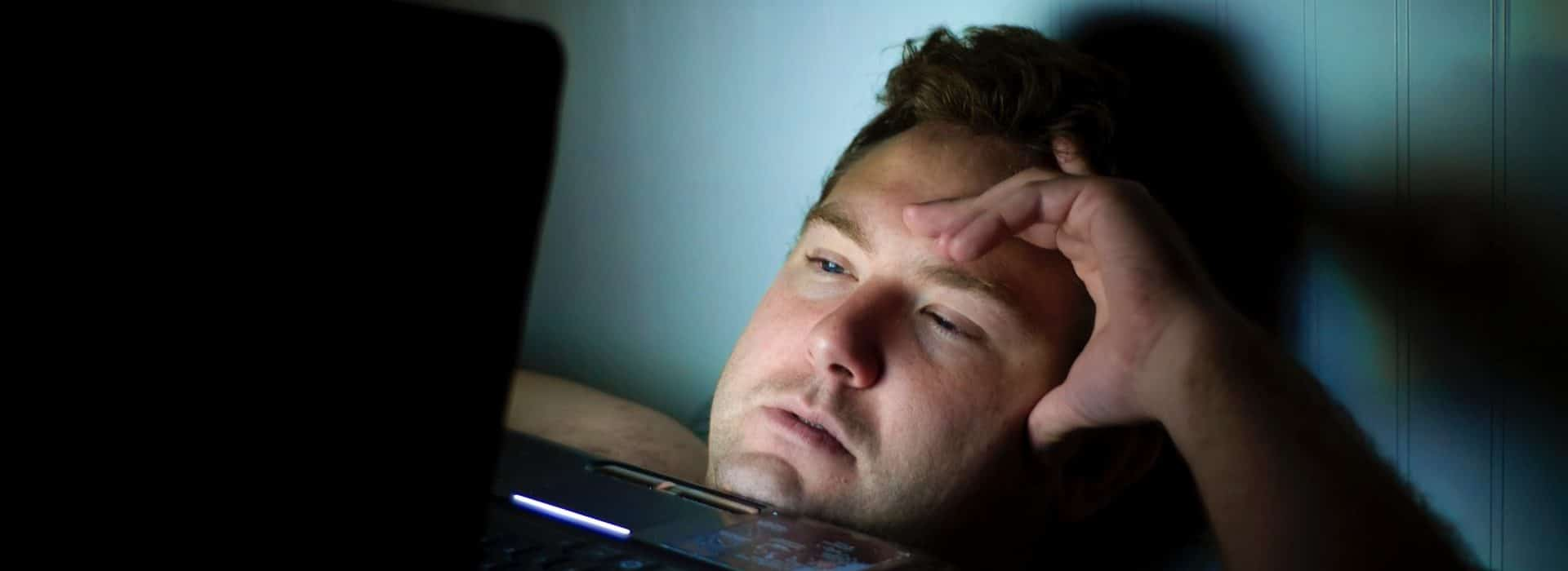 man awake on laptop in bed