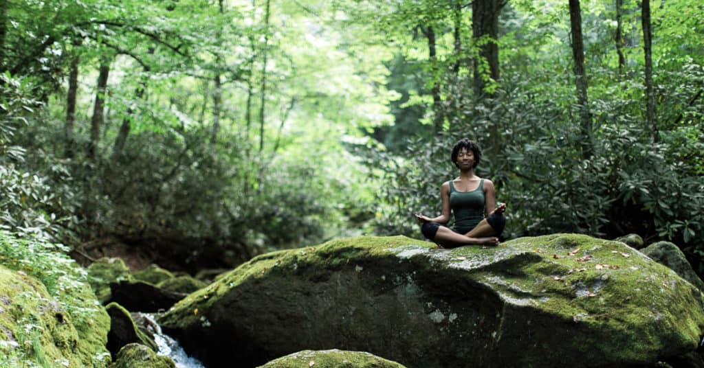 girl meditating on rock in green forrest