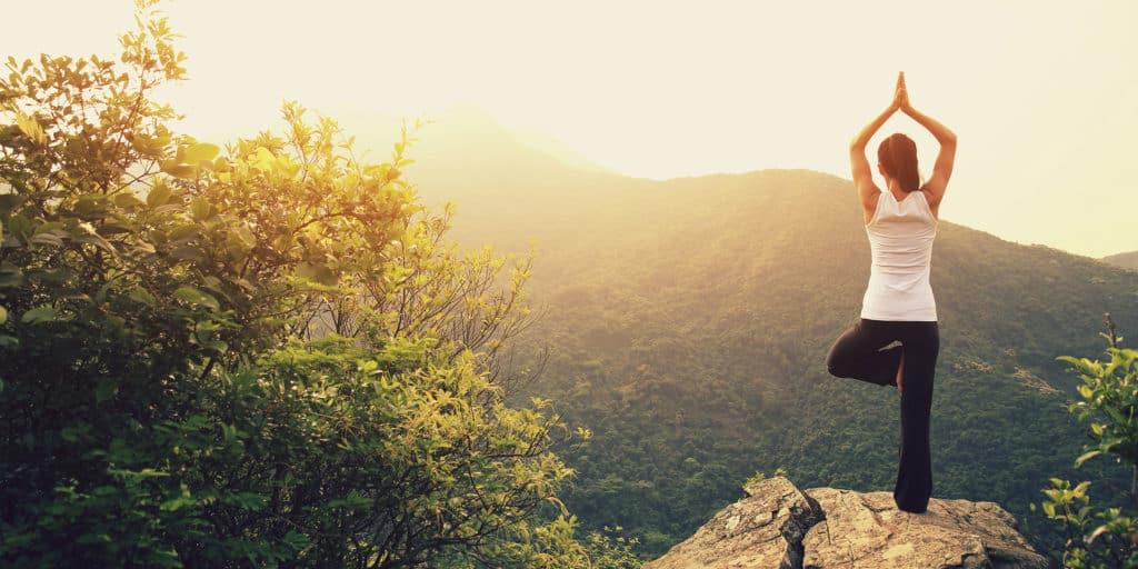 womend doing yoga on mountain top hero image