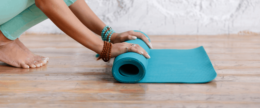 yoga mat on floor being rolled up