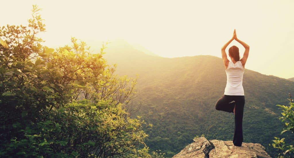 young fitness yoga woman at mountain peak