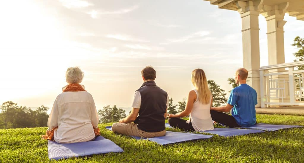 4 people meditating at sunrise