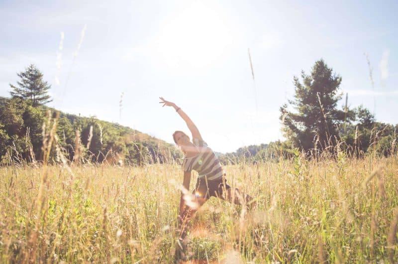 woman doing yoga in field